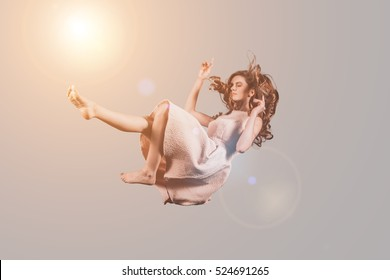 Falling to somewhere. Studio shot of attractive young woman hovering in air