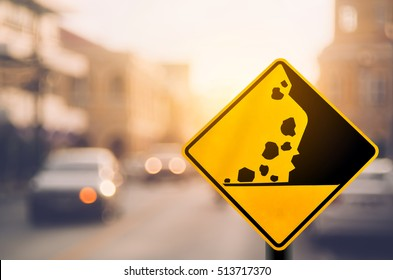 Falling stone warning traffic sign on blur road with colorful bokeh light abstract background. Copy space of travel and transportation concept. Vintage tone color filter style.