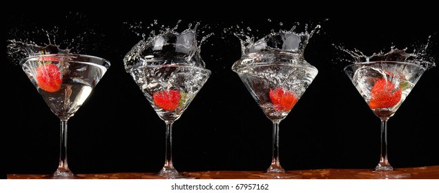 Falling strawberry in a glass with a drink