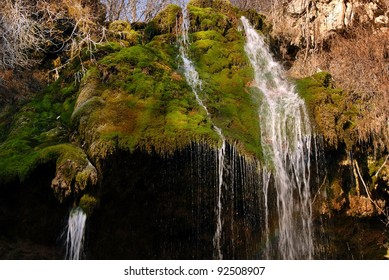 falling water stream over green moss at sunny day
