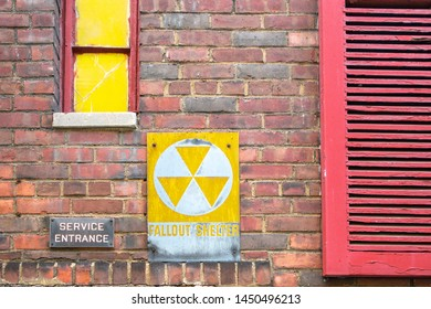 fallout shelter yellow white sign on the side of a New York City building with red shade with yellow pasinted window panes