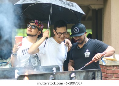 Falls Church, Va. - July 4, 2017: A group of young men grill meat on a rainy afternoon in a public space at  Bon Air Park.
