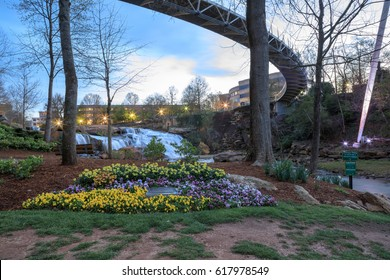 Falls Park on the Reedy River has picturesque waterfall views, a curved pedestrian suspension bridge, gardens, and a location in the historic west end of downtown Greenville, South Carolina.