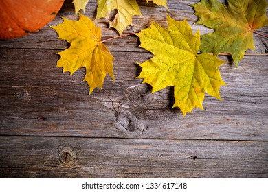 fall-still life with pumpkin and yellow maple leaves on wooden ground in top view