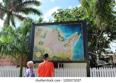 Falmouth, Jamaica: Dec. 4, 2017 – Man and woman tourists examine large outdoor street map of Falmouth Jamaica with its historical markers.