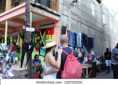 Falmouth, Jamaica: Dec. 4, 2017 –Man and woman tourists take selfie in market of main tourist area surrounded by street vendors