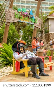 Falmouth, Jamaica - June 03 2015: Pirate Mascot sitting at the entrance to Jimmy Buffett's Margaritaville inside the Falmouth Cruise Port, Jamaica. Young smiling millennial couple posing for picture.