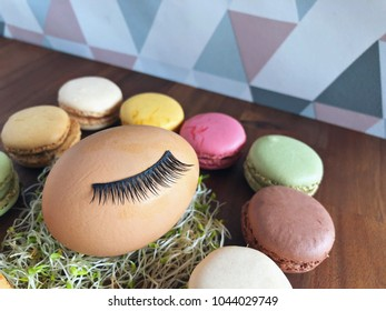 False eyelash extension on an easter egg decoration surrounded by pastel macaroons