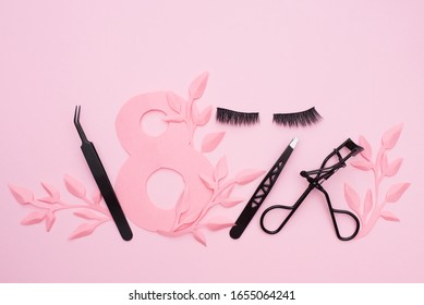 false eyelashes and black tweezers on pink backdround with paper leaves, copy space. World Women's Day, March 8th