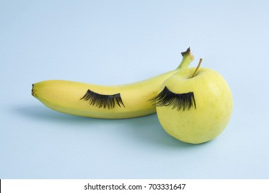 false eyelashes placed on different fruits. Minimal color still life and quirky photography