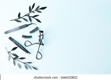False lashes with black tweezers and paper leaves on blue background with copy space