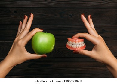 False teeth denture against green granny smith apple. Dental prosthesis care. Denture and Apple in the hands of a doctor. Dental care. Beautiful tooth. Prosthetics. False teeth