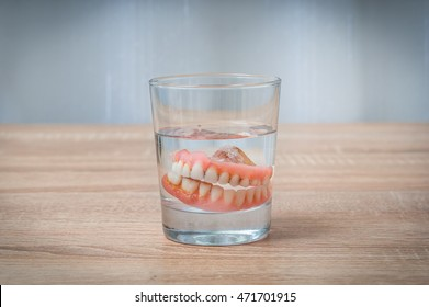 False teeth swim in transparent water glass - dental concept