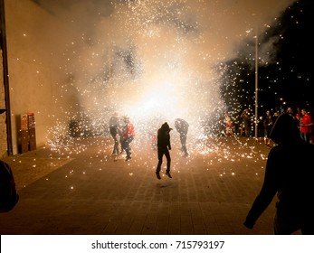 Falset, Tarragona, Catalonia, Spain - August, 18, 2017. Correfoc, typical catalan celebration in which devils armed with fireworks dance through the streets. Boy jumping.
