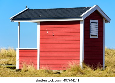 Falsterbo, Sweden - April 11, 2016: Red, white and black wooden beach hut or bathing cabin along the sandy shoreline. Dry grass and sand surround these small shacks.