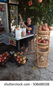 Famagusta, Cyprus - September 15 2016: Senior woman making fresh healthy pomegranate  juice with a fruit press machine.