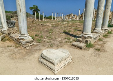 Famagusta, Turkish Republic of Northern Cyprus. Corinthian columns and heart shaped marble plinth stone at ancient city Salamis ruins. Sunny day, blue sky.