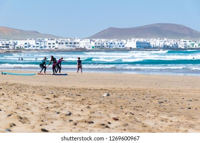 FAMARA BEACH, LANZAROTE ISLAND - DEC 15 2018: Surf lesson. Learners are about to enter the water at Famara beach, Canary Islands, Spain.