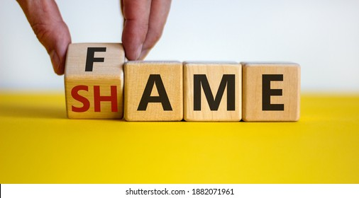 Fame or shame symbol. Male hand flips wooden cubes and changes the word 'shame' to 'fame' or vice versa. Beautiful yellow table, white background, copy space. Business and fame or shame concept.