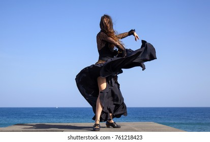 famenco by oceanside - slim attractive woman in a black and golden dress dances by oceanside