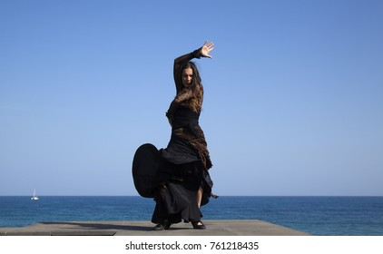 famenco by oceaside - slim attractive woman in a black and golden dress dances by oceanside