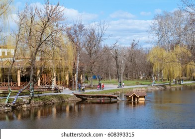 Families with children are walking along the lake in the city park in spring