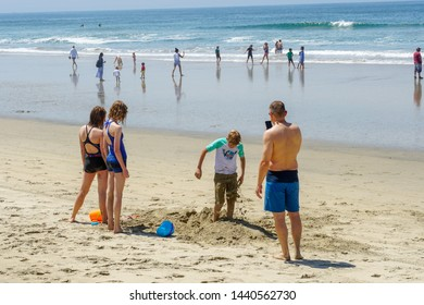 Families playing and building sand castle at the beach during beautiful summer day at Huntington Beach, California. USA  06/22/2019