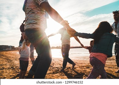 Families playing with children on the beach - Diverse culture people having fun on summer vacation at sunset - Travel, parenthood, holidays concept - Focus on center man feet