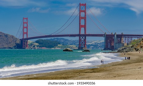 Families social distancing at Baker beach in view of the Golden Gate Bridge