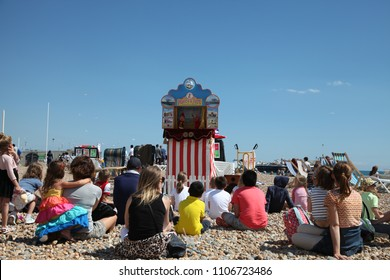Families watching a Punch and Judy show on the beach in Brighton Sussex England - July 31st 2016