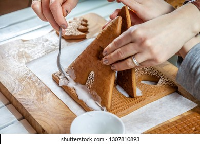 Familiy building a sweet ginger bread house.