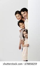 familiy hiding behind a huge board