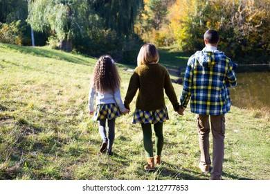 Familiy in similar cloth walking near river in autumn back view