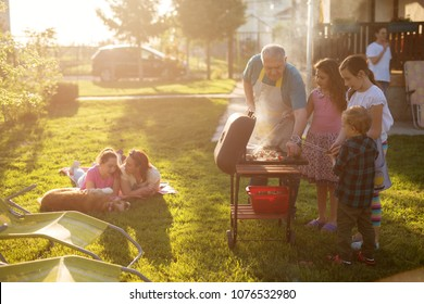 Familly enjoying picnic some are grilling some are laying on the blanket with a dog but everyone is having fun.