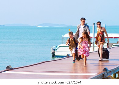 A family of 4 arriving at the resort with their luggage.