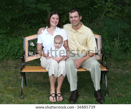 Family With A 4 Month Old Baby Poses On Bench In The Park