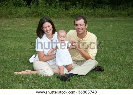 Family With A 4 Month Old Baby Poses In The Park Here They Are Sitting