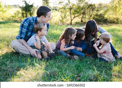 Family of 6 sit together in grass