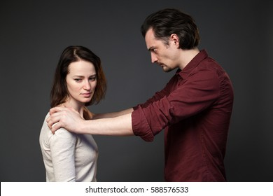 Family abuse - man is keeping woman's shoulders, she is looking to the side, gray background