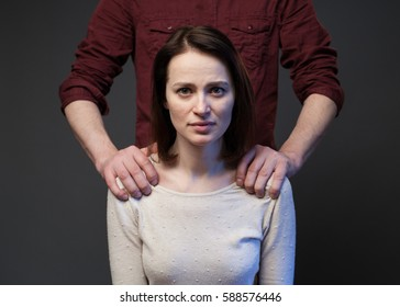 Family abuse - man's hands keeping woman's shoulders, gray background