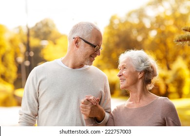 family, age, tourism, travel and people concept - senior couple walking in park