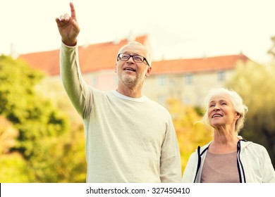 family, age, tourism, travel and people concept - senior couple pointing finger in city park