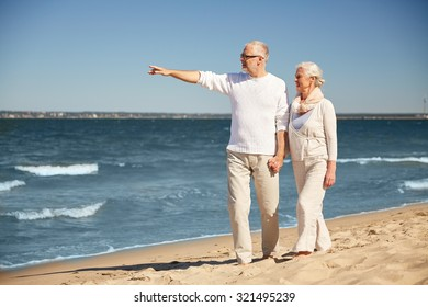 family, age, travel, tourism and people concept - happy senior couple walking and pointing finger to something on summer beach