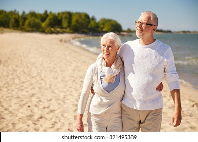family, age, travel, tourism and people concept - happy senior couple walking along summer beach