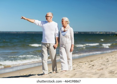 family, age, travel, tourism and people concept - happy senior couple walking and pointing finger on summer beach
