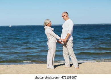 family, age, travel, tourism and people concept - happy senior couple holding hands on summer beach