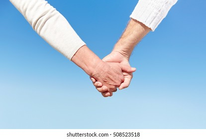 family, age, travel, tourism and people concept - close up of senior couple holding hands over blue sky background