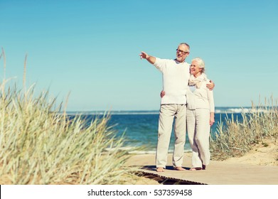 family, age, travel, tourism and people concept - happy senior couple hugging and pointing finger on summer beach