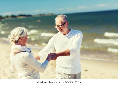 family, age, travel, tourism and people concept - happy senior couple holding hands and dancing on summer beach