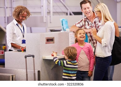 Family At Airport Check In Desk Leaving On Vacation